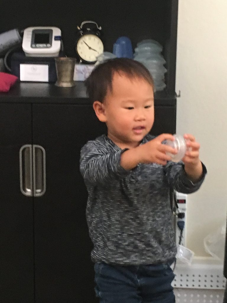 Young boy holding Chinese Medicine cups.