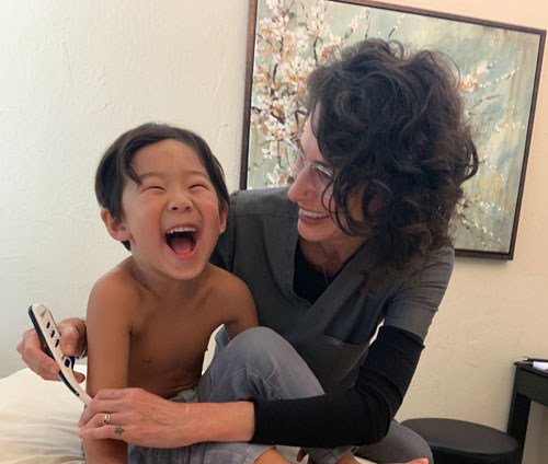 Young laughing boy with Dr. Den during acupuncture treatment.