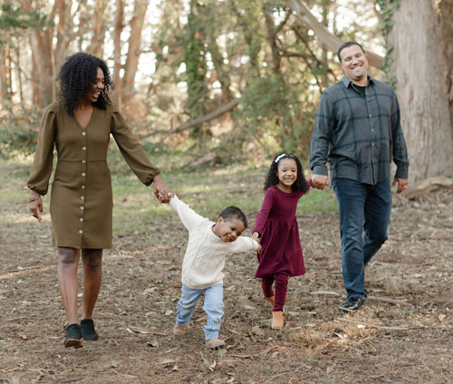 A couple and their two young kids walking hand-in-hand through a park.